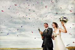 Happy wedding couple. Outdoor showered by confetti Stock Photo