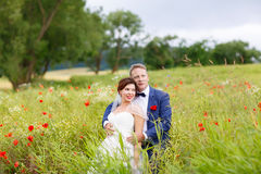 Happy wedding couple in pink poppy field Stock Photography