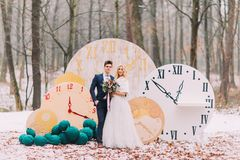 Happy wedding couple posing at the big vintage clocks in autumn forest. Creative decorations. Happy wedding couple posing at the big vintage clocks in autumn stock photography