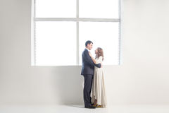Happy wedding couple posing in bright room embracing each other Stock Images