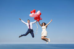 Happy wedding couple with red balloons Royalty Free Stock Photos