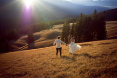 Happy wedding couple running and having fun on the field surrounded by mountains Royalty Free Stock Photo