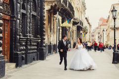 Happy wedding couple runs along the old street with great archit. Ecture Royalty Free Stock Image