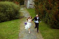 Happy wedding couple runs in the park Stock Photos