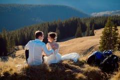 Happy wedding couple sitting on the mountain peak. Sunny day in Alps Stock Photo