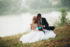 Happy Wedding Couple Sitting On The Ground Near The Lake Royalty Free Stock Photography