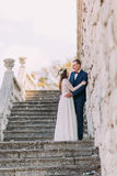 Happy wedding couple stand on antique stone stairs. Full length portrait.  Royalty Free Stock Image