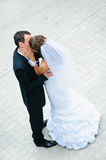 Happy wedding couple standing, kissing and embracing Stock Photo
