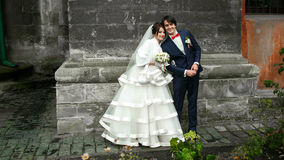 Happy wedding couple stands behind a gray stone wall somewhere i. N the city Royalty Free Stock Photos