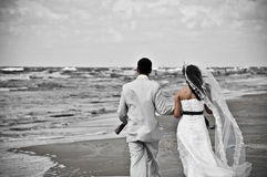 Happy wedding couple walking along seashore Stock Images