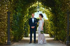 Happy wedding couple is walking by a beautiful garden. stock photos