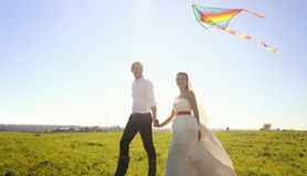 Happy wedding couple walking on green field with flying kite. Summer outdoor stock images