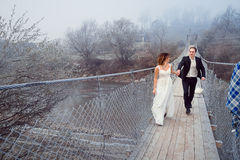 Happy wedding couple walking and laughing on the wooden bridge. Honeymoon at mountains Stock Photography