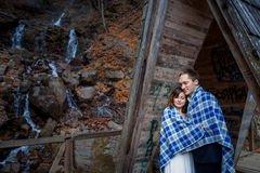 Happy wedding couple wrapped in blanket tenderly hugs with eyes closed. Wodden bridge at the mountains Royalty Free Stock Image