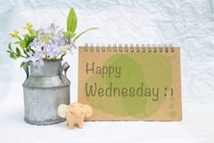Happy Wednesday on design notebook cover with smiling elephant clay doll and flower pot. Over blurred background, greeting card concept stock photo
