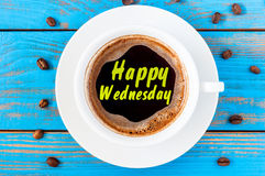 Happy Wednesday on top view coffee cup at blue wooden background with beans.  stock photo
