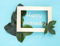 Happy wednesday in wooden picture frame with beautiful green leaves. On wooden blue background stock photo
