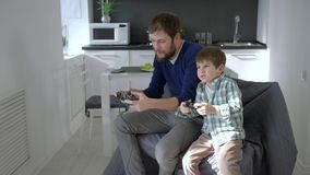 Happy weekend, cheerful daddy with child play video game sitting on chair. Happy weekend of gamers, cheerful daddy with child play video game sitting on chair stock video