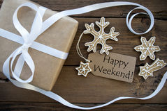 Happy Weekend Greetings with Winter Background. Happy Weekend Greetings on Natural Label on Wood Decorated with Gift Box and Ginger Bread Cookies, Christmas or royalty free stock photo