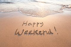 Happy weekend. Greeting card written on sand stock photos