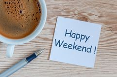 Happy Weekend message at peace of paper on office desk with morning coffee cup Royalty Free Stock Photos