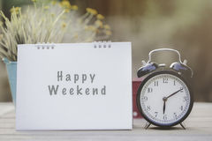 Happy weekend note on morning sunlight with alarm clock Stock Images