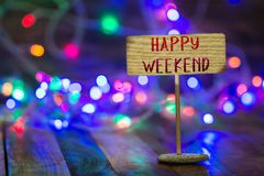 Happy weekend on small sign board. Happy weekend written on small wooden sign board on wooden table with Christmas light and bokeh background stock photos