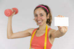 Happy weight loss woman showing empty card. Happy smiling weight loss woman lifting a dumbbell and showing a blank sign card for marketing on grey background Royalty Free Stock Photo
