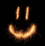 Happy weird smiling smiley drawn with sparkles on black background Stock Photography