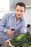 Happy well looking man drinking red wine in the kitchen Stock Image