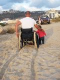 Happy Wheelchair Family. Proud father in wheelchair with his baby girl enjoying time on the beach Stock Image