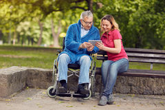 Happy wheelchair man with daughter using tablet. Happy wheelchair men with daughter using tablet in the park Stock Photography