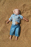 Happy white baby lying outstretched hands on the grain.  Stock Photos