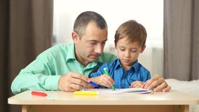 Happy white family at home. Father and child helps son to draw. Education, parenthood and relationships, teaching