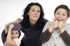 Happy white family smiling. Beautiful mother and her children posing in studio Stock Photos