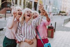 Three stylish women making a funny selfie stock photo