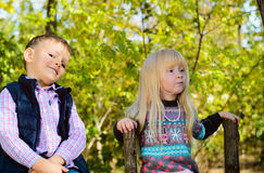 Happy White Kids Sitting on Wooden Garden Fence Royalty Free Stock Image