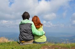 Happy white man and woman tourists in green clothes sitting hugging on edge of top of mountain and look into distance stock photo