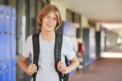Happy white teenage boy smiling in high school corridor Stock Image