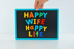 Happy wife happy life with magnetic colored letter blocks on blackboard Royalty Free Stock Images