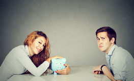 Happy wife with piggy bank sitting across the table from sad husband Stock Photos