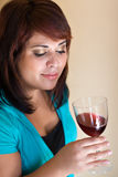 Happy Wine Taster. A young woman holding a glass of red wine Stock Photo