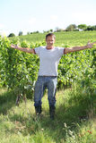 Happy winegrower. Winegrower standing in vineyard with stretched arms Royalty Free Stock Photography