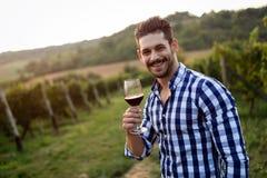 Winegrower tasting wine in vineyard Stock Photos