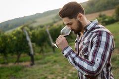 Winegrower tasting wine in vineyard Stock Image