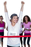 Happy winner athlete crossing finish line with arms raised Stock Photography