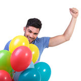 Happy winner of a bunch of baloons celebrating Stock Images