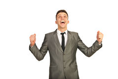 Happy winner business man. Looking up and cheering isolated on white background stock images