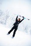Happy winner female skier. Happy winner girl holding skis up Royalty Free Stock Photo