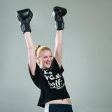 Happy winner girl in box gloves. Success concept. Happy winner girl in box gloves on gray studio background. Success concept Stock Photo